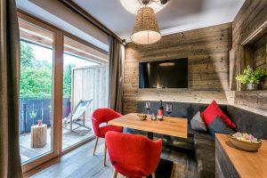 Familienzimmer - Sitzecke mit roten Stühlen
