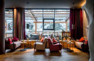 Lounge mit bunten Sofas und großer Fensterfront mit Blick auf verschneite Terrasse