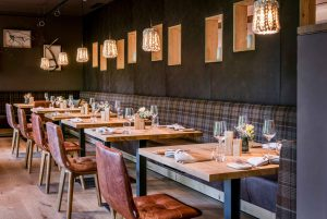 Restaurant mit Tischen und Stühlen in dunklen Farben