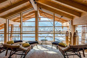 Wellnessbereich mit Liegen in einer Raum mit offenen Giebel und Blick auf verschneite Berge