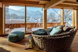 Liege mit Kissen vor großem Fenster mit Blick auf die Berge