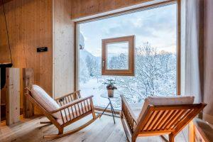 Zwei Schaukelstühle vor großem Fenster mit Blick auf Schneelandschaft
