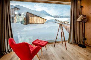 Roter Sessel und großes Fernglas mit Blick auf die Berge