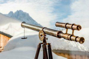 Altes antikes Fernglas mit Blick auf verschneite Berge