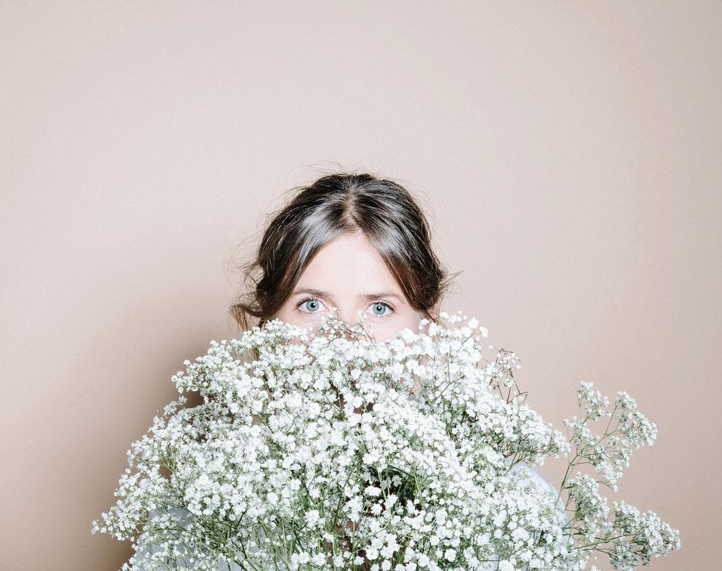 Frau mit Blütenstrauß vor dem Gesicht