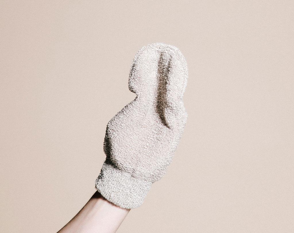 Hand mit Peelinghandschuh