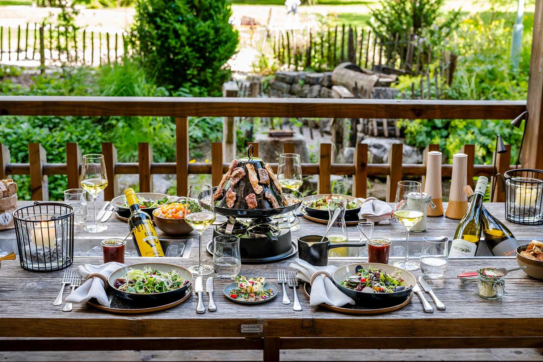 Hutessen auf der Terrasse mit Fleisch, Salaten und Aufstrichen