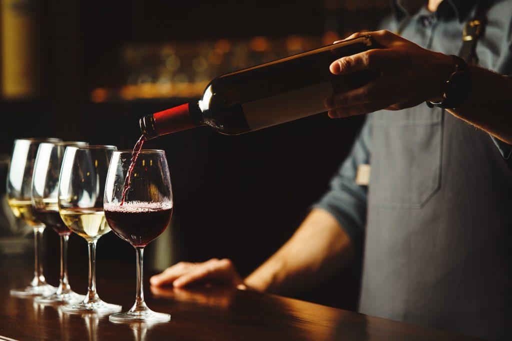 Mann mit grauer Schürze schenkt Wein in Weingläser ein